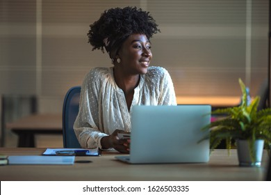 Smiling African woman looking out of a window while sitting at a table working online with a laptop. Businesswoman using laptop in office. Smiling african american female freelancer working at office
