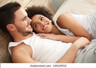Smiling African woman lying in bed with her boyfriend.