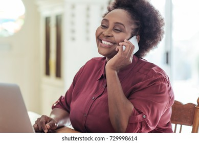 Smiling African woman sitting alone at her kitchen table at home working online with a laptop and talking on a cellphone