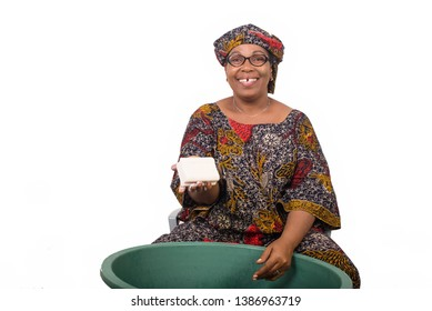Smiling african woman sitting and washing clothes in a green bowl grade and showing a big piece of soap to the white camera isolated on white background.