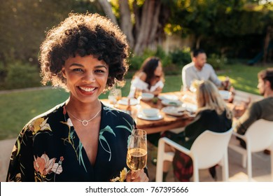 Smiling african woman standing outdoors with people sitting in background having food at party. Woman with a drinks at outdoor party.