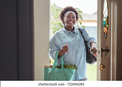Smiling African woman walking through the front door of her home with a shopping bag full of fresh produce