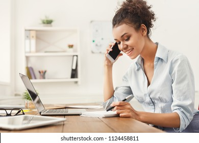 Smiling african-american business woman at work talking on phone and taking notes, sitting at her working place in office, copy space
