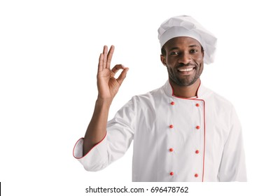 smiling african-american chef showing okay sign isolated on white