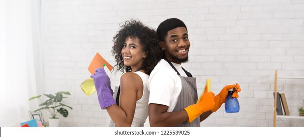 Smiling african-american couple holding spray detergents, housekeeping and cleaning service concept