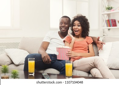 Smiling african-american couple relaxing and watching TV at home, eating popcorn, having rest after hard week, copy space