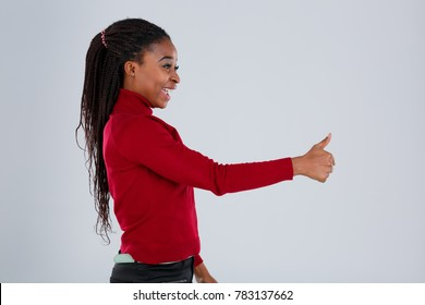 Smiling African-American girl stands sideways and shows in front of herself a thumbs-up gesture.