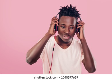 smiling African-American man in headphones listening to music on pink background