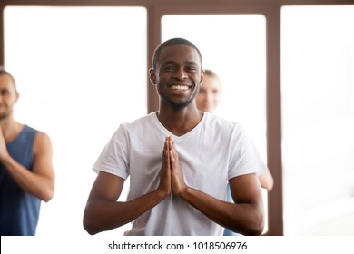 Smiling african-american man holding hands in namaste gesture, happy black positive guy ready to start practicing yoga meditation exercises at group training class together with multiracial people