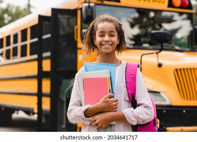 Smiling african-american schoolgirl going back to school with books and copybooks waiting for schoolbus. New academic year semester