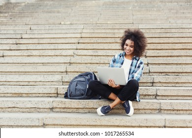 Smiling african-american student girl sitting on stairs working on laptop, preparing for exams outdoors, having rest in university campus. Technology, education and remote working concept, copy space
