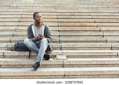 Smiling african-american student sitting outdoors on university stairs with smartphone, typing, surfing internet, preparing for exams. Technology, education and remote working concept, copy space