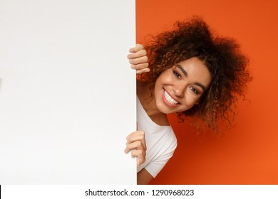 Smiling african-american woman looking out of white blank sign with copy space on orange background