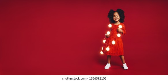 Smiling afro american girl playing with christmas lights. Kid standing against red background wearing fairy lights.