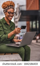 Smiling Afro American lady sitting on the bench outdoors and using credit card for online shopping. Online shopping concept. Happy young woman using laptop for online shopping in the city