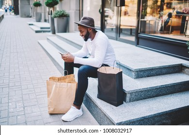 Smiling afro american male customer in trendy hat sitting on stairs of store waiting for delivery service sending email on mobile, dark-skinned guy satisfied with online shopping resting with bags