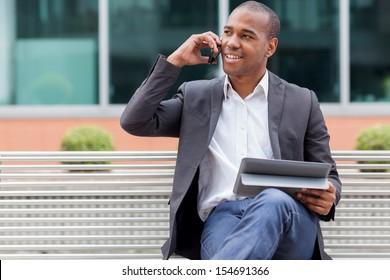 Lächeln nach amerikanischem Manager auf einer Bank und telefonieren