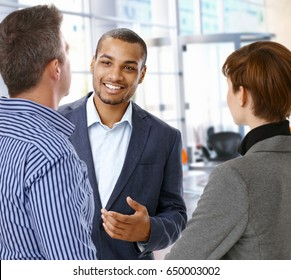 Smiling afro american office worker at business meeting with colleagues, gesturing, focus in background.