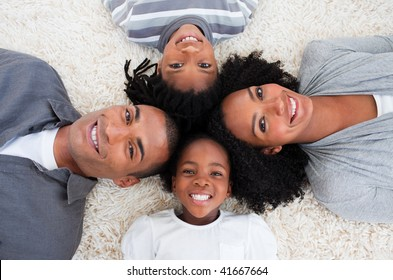 Smiling Afro-American family on floor with heads together