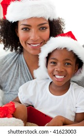 Smiling Afro-American mother and daughter opening a Christmas gift