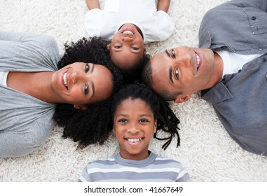 Smiling Afro-American young family lying on floor in a circle
