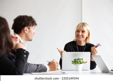 Smiling aged business woman talking and looking at colleague while team meeting, Happy attentive female team leader and coach listening and developing for new project idea