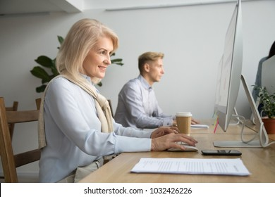 Smiling aged businesswoman office worker working on pc desktop computer at modern workplace, happy attractive senior woman employee browsing online using corporate applications software for business