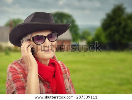 abe348dce51e ... Stock Photo (Edit Now) 287309111 - Shutterstock. Smiling aged cowgirl  is talking on smart phone. Old woman in sunglasses is wearing black