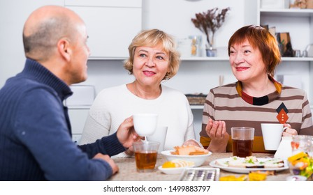 Smiling aged friends are sitting at table with tea and talking about life at home.