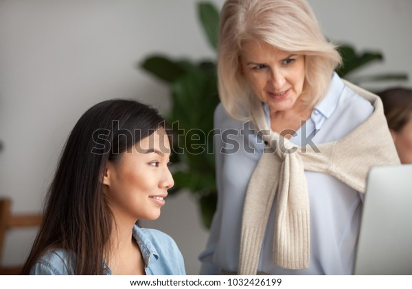 Smiling aged leader checking computer online work of asian employee looking at pc screen, friendly senior woman mentor helping new worker, teaching young manager or supervising intern in office