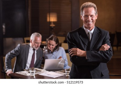 Smiling aged man standing with crossed arms in the restaurant