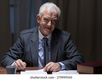 Smiling aged man working in the evening in his office