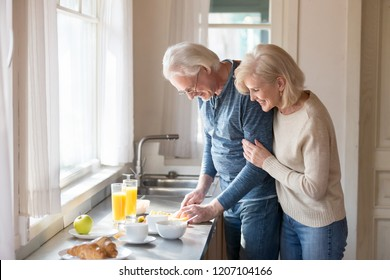 Smiling aged wife hug man from behind watching him preparing healthy food, loving senior woman embrace husband cooking breakfast slicing fruit, romantic couple spend morning at home together
