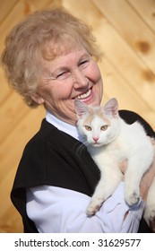 Smiling aged woman with cat on hands, focus on cat