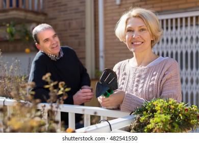 Smiling aged woman with horticultural sundry and aged man drinking tea in patio