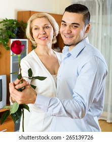 Smiling aged woman and young boyfriend dancing indoors. Focus on the man