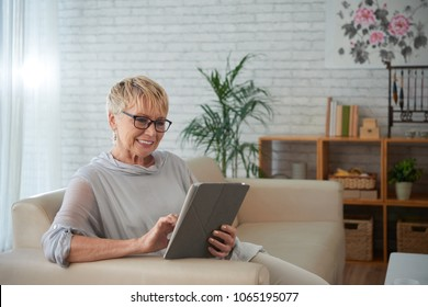 Smiling aged young woman using application on tablet computer