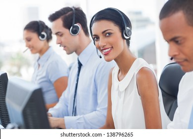 Smiling agent with colleagues sitting next to her