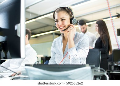 Smiling agent woman with headsets. Portrait of call center worker at office.