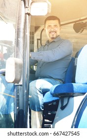 smiling agricultural worker sitting in cabin of agrimotor  with large wheels