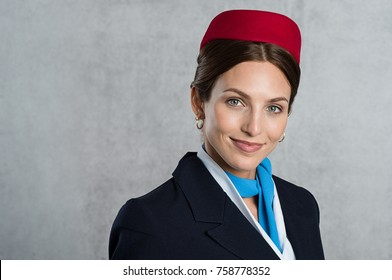 Smiling air hostess looking at camera. Successful flight assistant wearing uniform isolated over grey background. Young stewardess looking at camera and smiling.