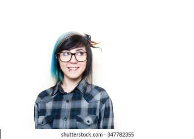 Smiling alternative teen woman in blue shirt looking up her left isolated