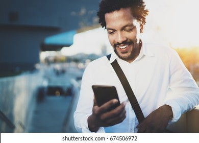 Smiling American African man using smartphone to text message friends at sunny street.Concept of happy young handsome people enjoying gadgets outdoors.Blurred background