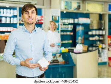 smiling american handsome man   in pharmacy drugstore