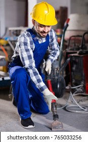 Smiling american working man practicing his skills with pneumatic drill at workshop