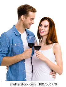 Smiling amorous amazed couple drinking red wine. Portrait image of models with redwine glasses in love studio valentin day concept isolated over white background. Man and woman together 14 february ad