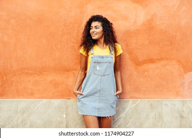 Smiling Arab Girl with black curly hairstyle looking left side. African female in casual clothes in the street. Happy woman wearing yellow t-shirt and denim dress in urban background.