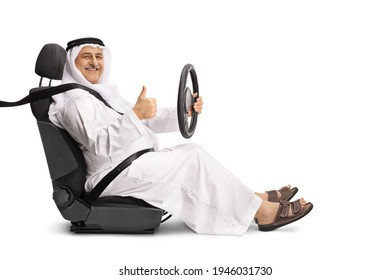 Smiling arab man in a driver seat holding the steering wheel and showing a thumb up sign isolated on white background