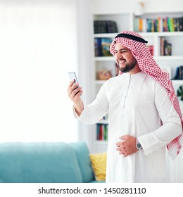 smiling arab man talking by video conference at home