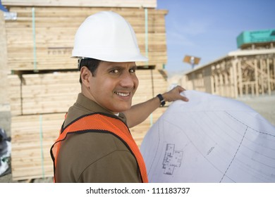 Smiling architect with blueprint at construction site